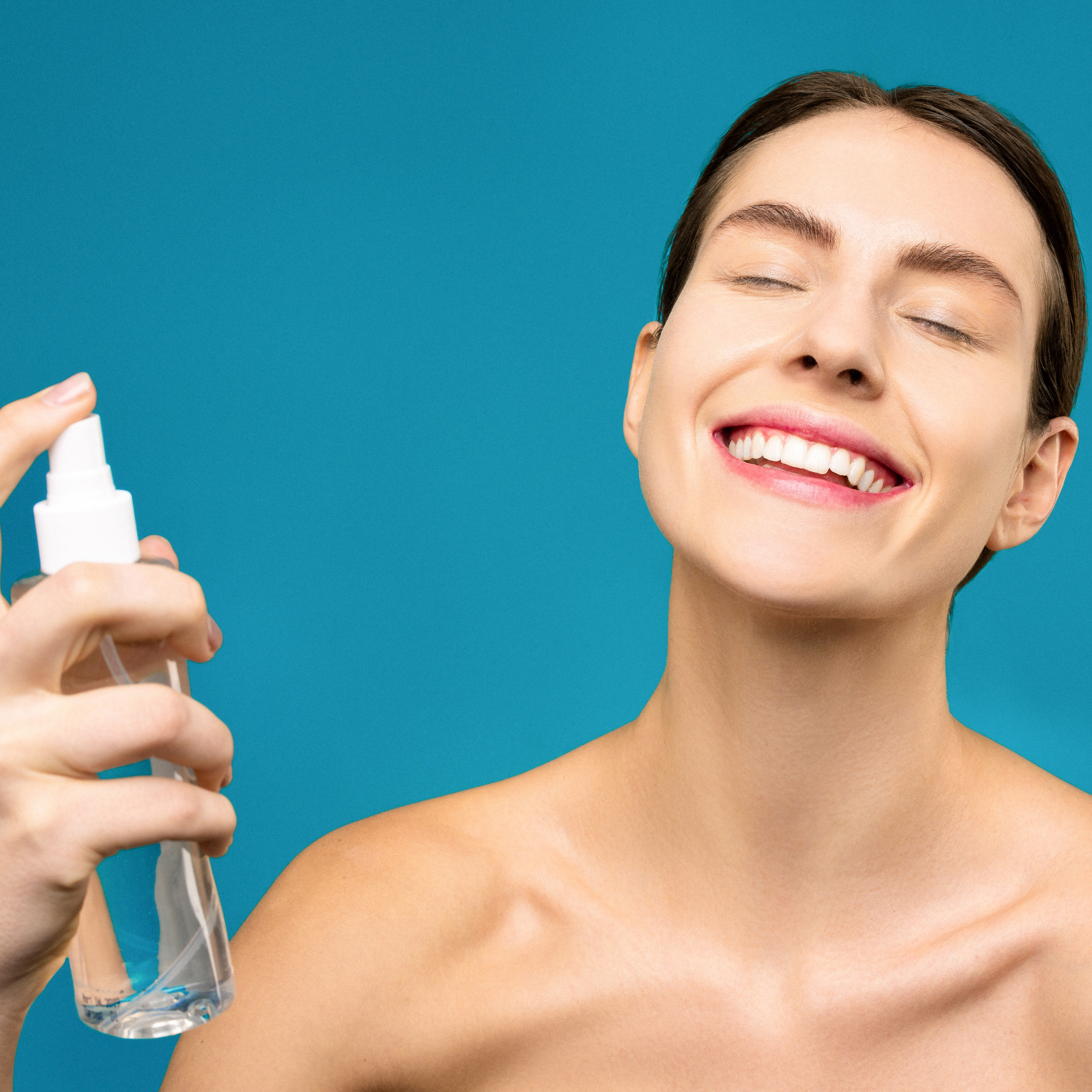 smiling-woman-holding-clear-spray-bottle-3762561