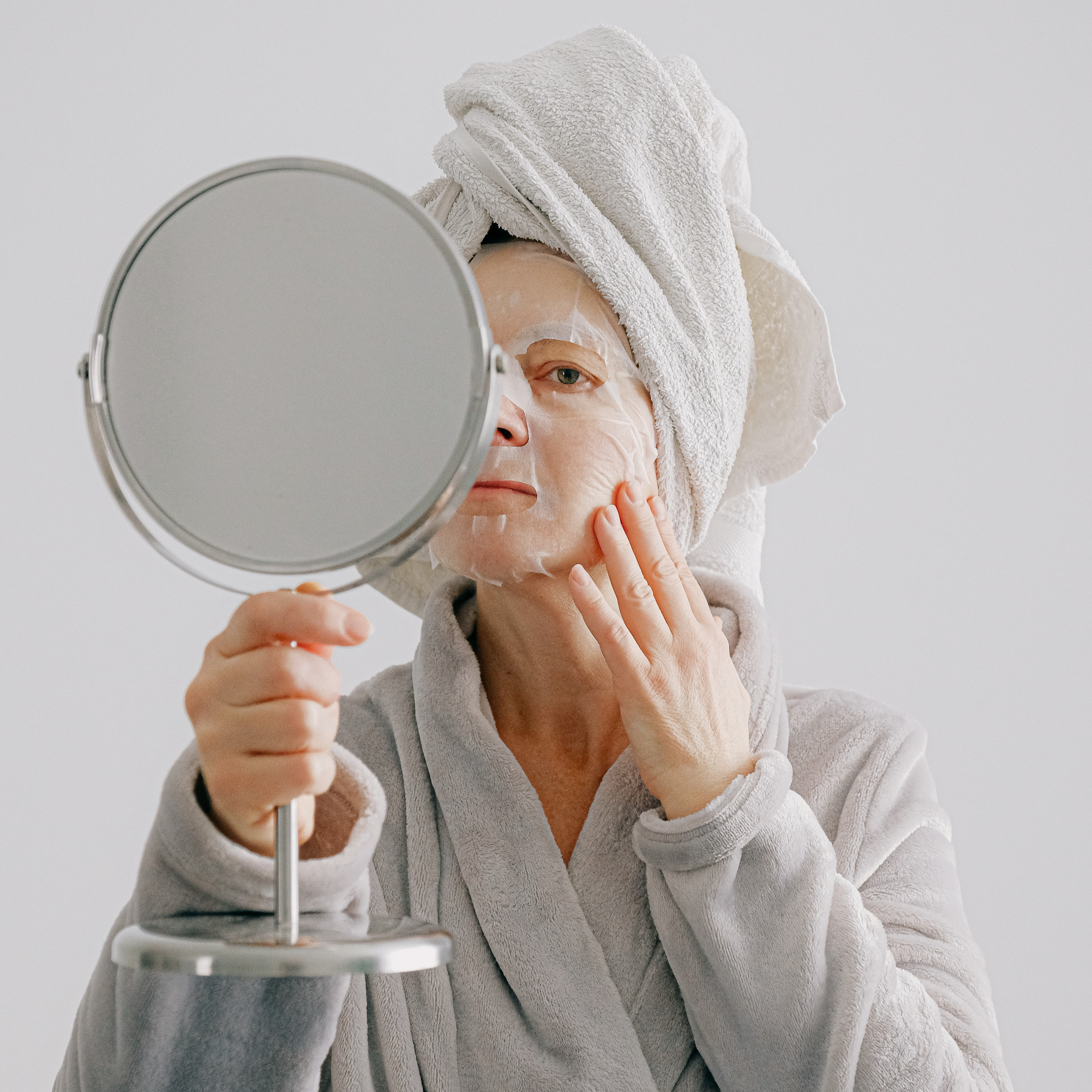 person-in-gray-bathrobe-holding-round-mirror-3846099